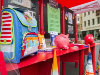 Ein Stand mit Schulranzen und Sparschweinen zum Spendensammeln