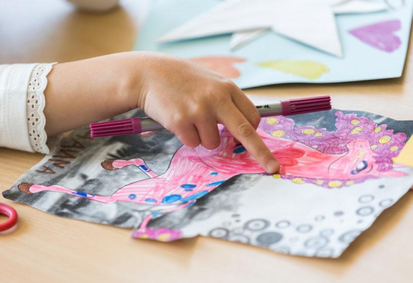 Ein Kind malt ein Einhornbild aus.